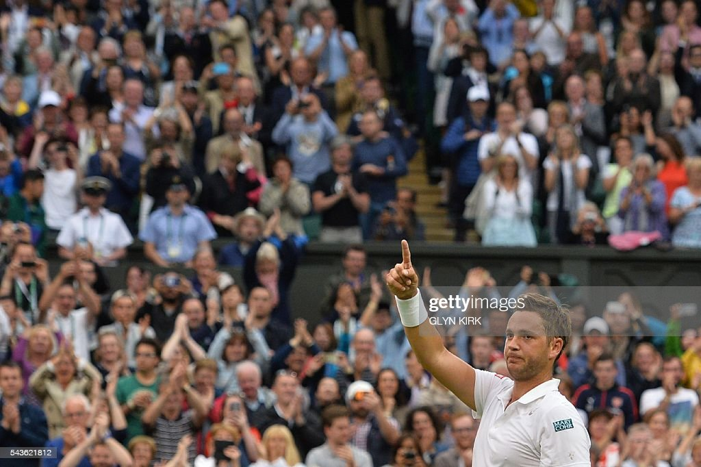 Britain's Marcus Willis salutes the crowd after Switzerland's Roger Federer won their men's singles second round match on the third day of the 2016 Wimbledon Championships at The All England Lawn Tennis Club in Wimbledon, southwest London, on June 29, 2016. / AFP / GLYN
