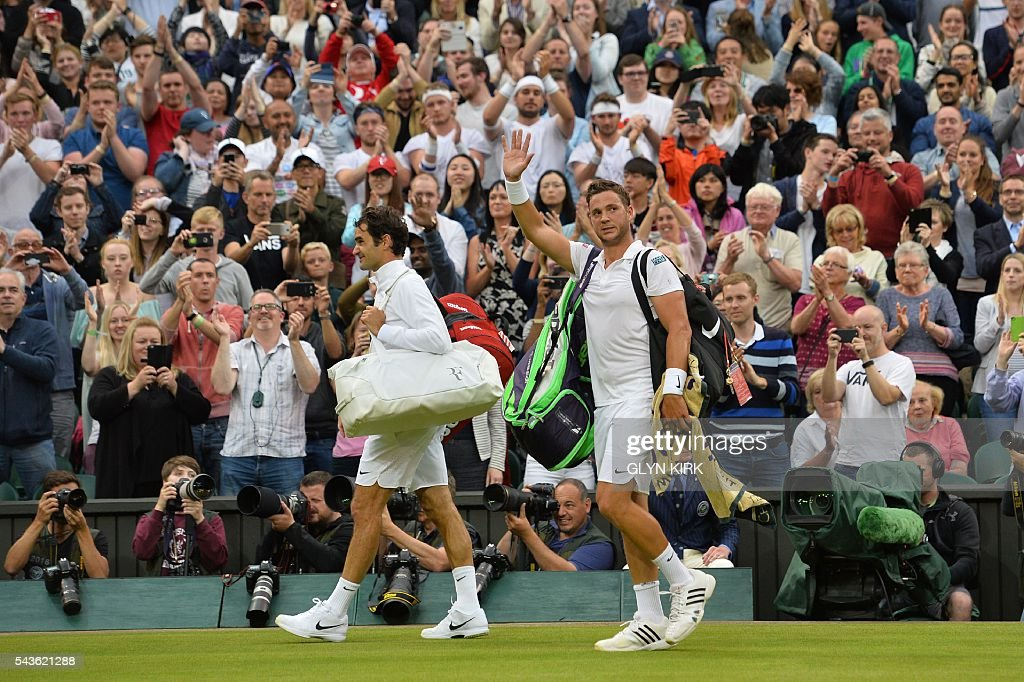 Britain's Marcus Willis (R) waves as he leaves the court with Switzerland's Roger Federer (L) after Federer won their men's singles second round match on the third day of the 2016 Wimbledon Championships at The All England Lawn Tennis Club in Wimbledon, southwest London, on June 29, 2016. / AFP / GLYN