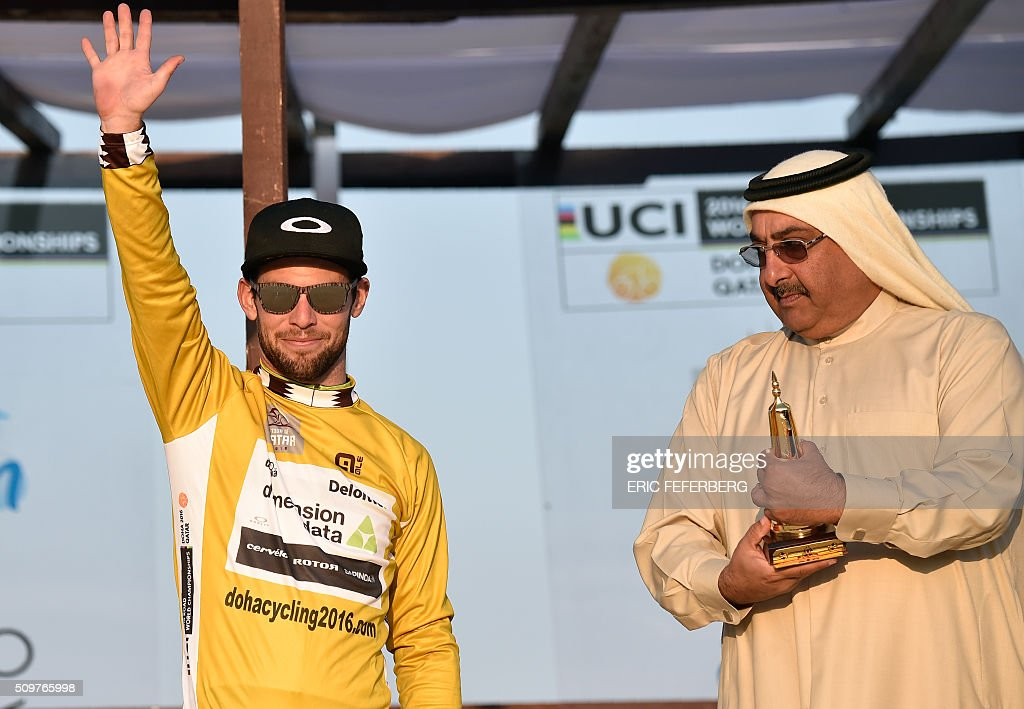 Britain's Mark Cavendish (L) of Dimension Data team celebrates with the overall gold jersey as Qatar cycling federation Sheikh Khalid Bin Ali al-Thani (R) presents him with a trophy on the podium following the 5th and last stage of the 15th Tour of Qatar on February 12, 2016, in Qatar. / AFP / ERIC FEFERBERG