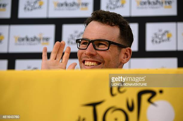 Britain's Mark Cavendish waves to his daughter as he takes part in the press conference of the Belgium's Omega Pharma Quick Step cycling team on July...