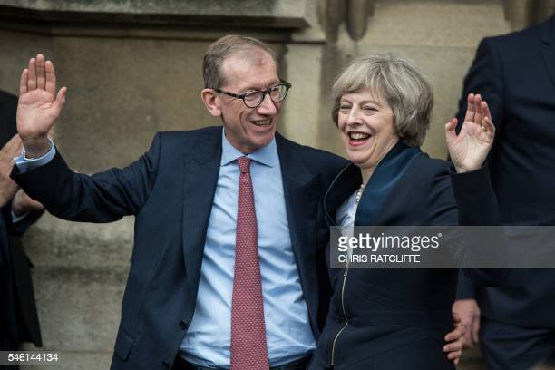 Britain's new Conservative Party leader Theresa May and her husband Philip John May wave after speaking to members of the media at The St Stephen's...