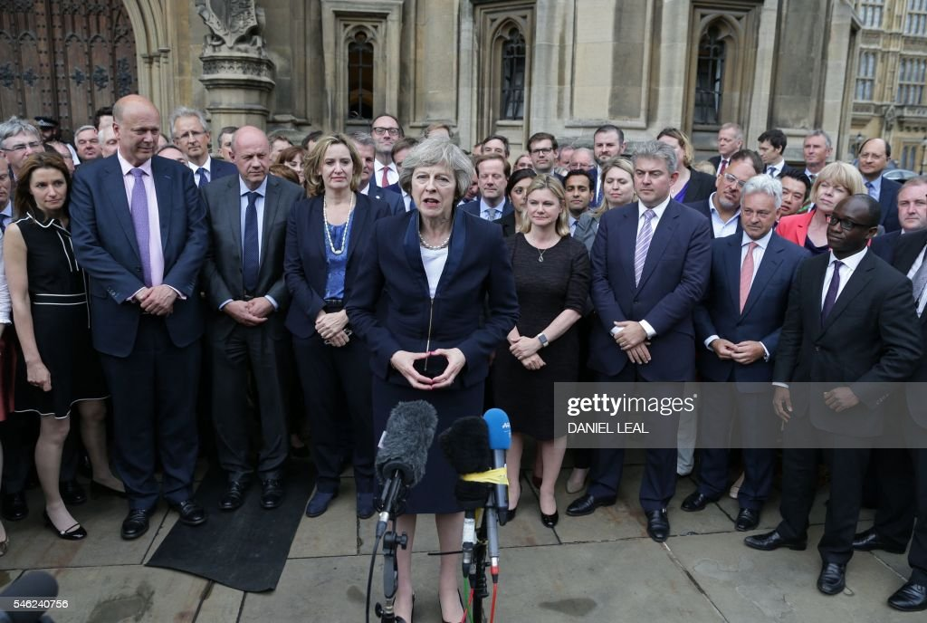 Britain's new Conservative Party leader Theresa May (C), flanked by her supporters, speaks to members of the media at The St Stephen's entrance to the Palace of Westminster in London on July 11, 2016. Theresa May will on Wednesday become the prime minister who leads Britain's into Brexit talks after her only rival in the race to succeed David Cameron pulled out unexpectedly. May was left as the only contender standing after the withdrawal from the leadership race of Andrea Leadsom, who faced criticism for suggesting she was more qualified to be premier because she had children. OLIVAS