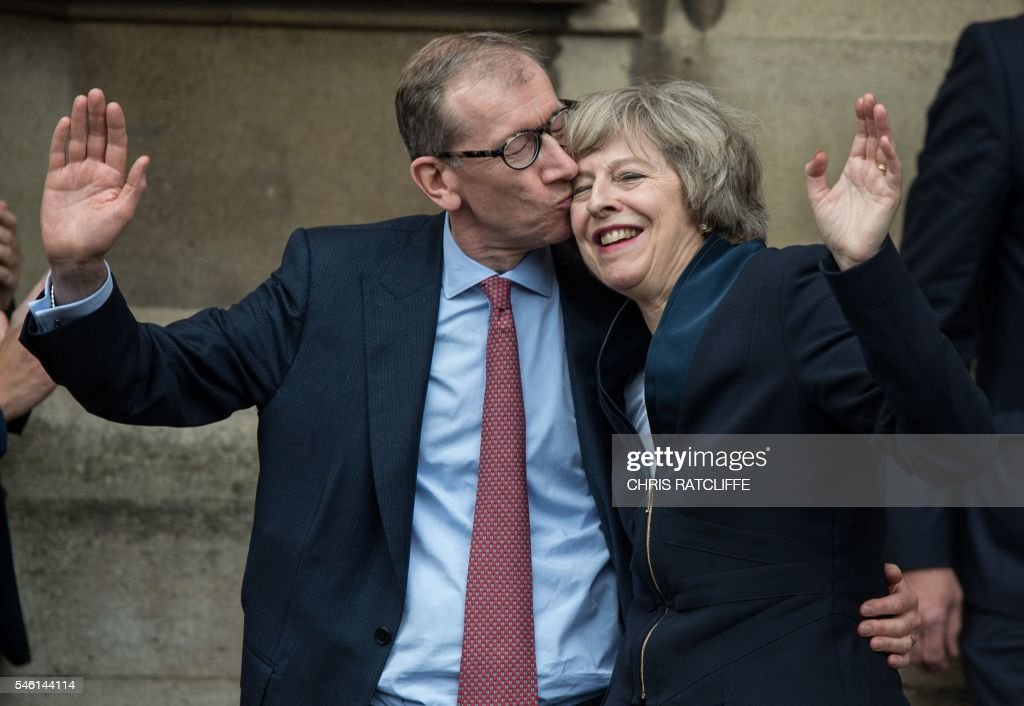 Britain's new Conservative Party leader Theresa May (R) receives a kiss from her husband Philip John May (L), after speaking to members of the media at The St Stephen's entrance to the Palace of Westminster in London on July 11, 2016. Theresa May will on Wednesday become the prime minister who leads Britain's into Brexit talks after her only rival in the race to succeed David Cameron pulled out unexpectedly. May was left as the only contender standing after the withdrawal from the leadership race of Andrea Leadsom, who faced criticism for suggesting she was more qualified to be premier because she had children. RATCLIFFE