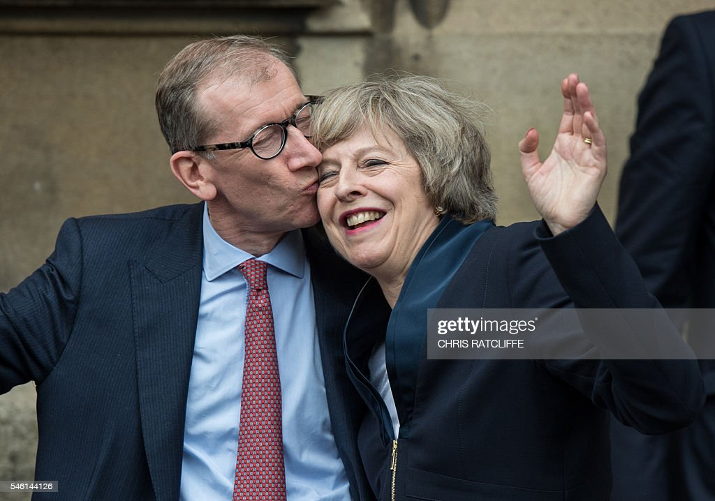 TOPSHOT - Britain's new Conservative Party leader Theresa May (R) receives a kiss from her husband Philip John May (L), after speaking to members of the media at The St Stephen's entrance to the Palace of Westminster in London on July 11, 2016. Theresa May will on Wednesday become the prime minister who leads Britain's into Brexit talks after her only rival in the race to succeed David Cameron pulled out unexpectedly. May was left as the only contender standing after the withdrawal from the leadership race of Andrea Leadsom, who faced criticism for suggesting she was more qualified to be premier because she had children. RATCLIFFE
