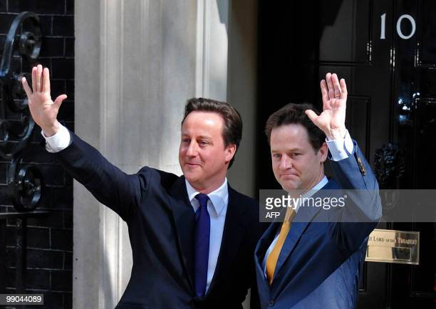 Britain's new Prime Minister David Cameron and new Deputy Prime Minister Nick Clegg wave as they pose for pictures outside 10 Downing Street in...