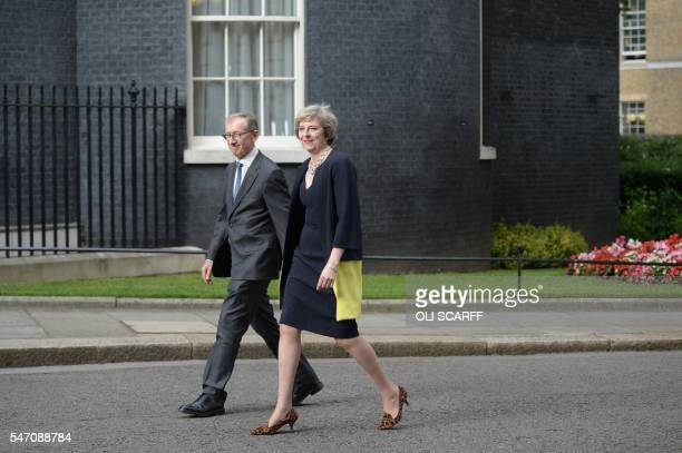 Britain's new Prime Minister Theresa May and her husband Philip John walk up Downing Street in central London on July 13 2016 on the day she takes...