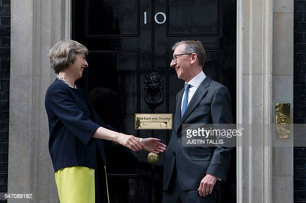 Britain's new Prime Minister Theresa May and her husband Philip John look at each other outside 10 Downing Street in central London on July 13 2016...