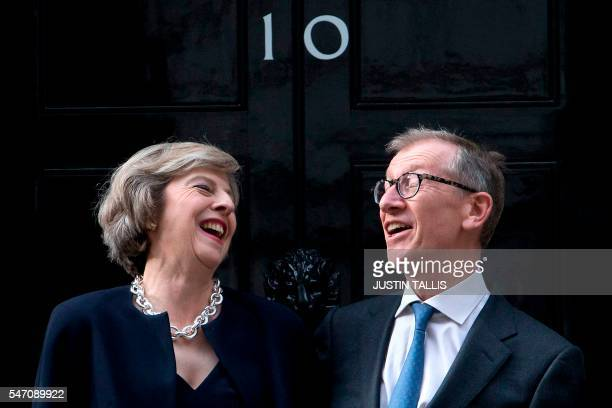 TOPSHOT Britain's new Prime Minister Theresa May and her husband Philip John May laugh together outside the door of 10 Downing Street in central...