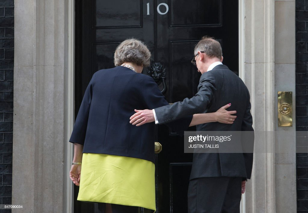 Britain's new Prime Minister Theresa May and her husband Philip John (R) walk towards 10 Downing Street in central London on July 13, 2016 on the day she takes office following the formal resignation of David Cameron. Theresa May took office as Britain's second female prime minister on July 13 charged with guiding the UK out of the European Union after a deeply devisive referendum campaign ended with Britain voting to leave and David Cameron resigning. TALLIS