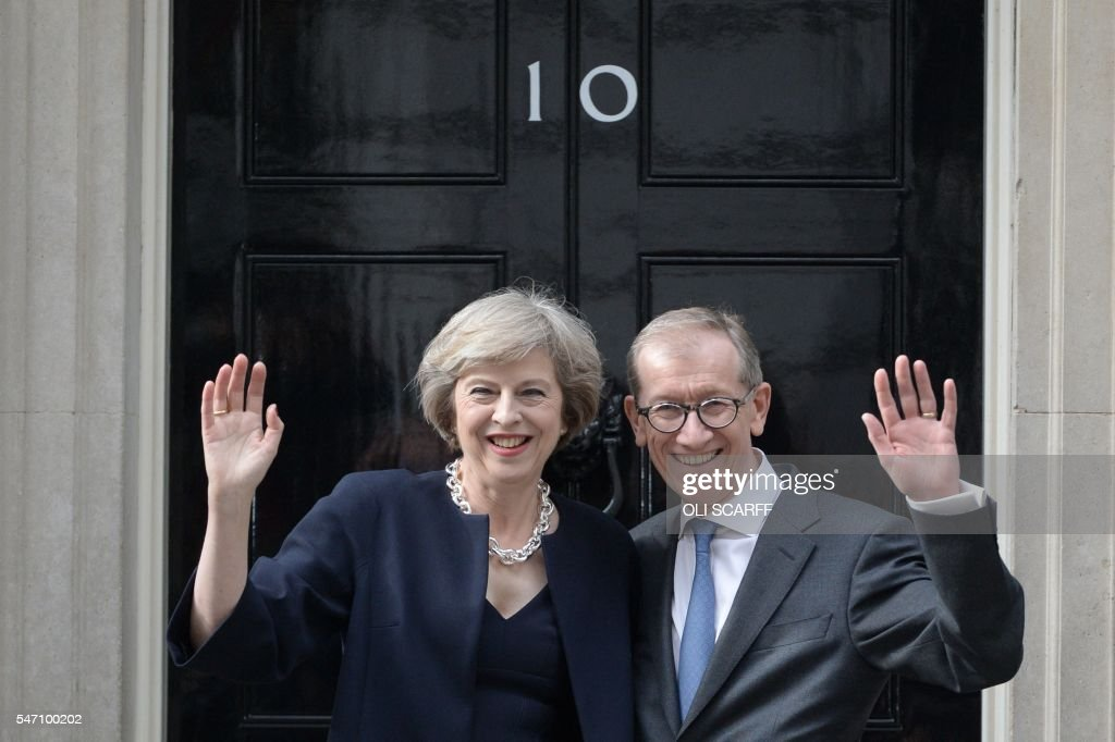 Britain's new Prime Minister Theresa May and her husband Philip John (R) wave outside 10 Downing Street in central London on July 13, 2016 on the day she takes office following the formal resignation of David Cameron. Theresa May took office as Britain's second female prime minister on July 13 charged with guiding the UK out of the European Union after a deeply devisive referendum campaign ended with Britain voting to leave and David Cameron resigning. SCARFF