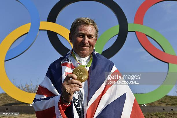 Britain's Nick Skelton celebrates with his gold medal in front of the Olympic rings after the individual equestrian show jumping event during the Rio...