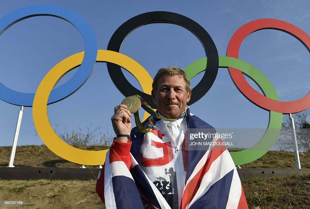 Britain's Nick Skelton celebrates with his gold medal in front of the Olympic rings after the individual equestrian show jumping event during the Rio 2016 Olympic Games in Rio de Janeiro on August 19, 2016. / AFP / John MACDOUGALL
