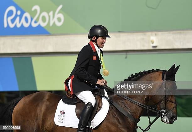 Britain's Nick Skelton on his horse Big Star rides with his gold medal after winning the individual equestrian show jumping event at the Olympic...