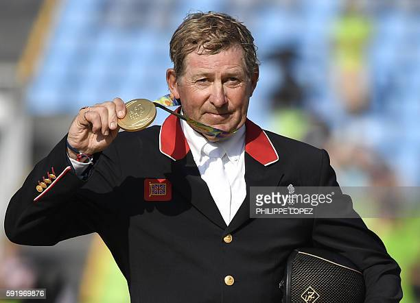 Britain's Nick Skelton poses with his gold medal in the individual equestrian show jumping event at the Olympic Equestrian Centre during the Rio 2016...