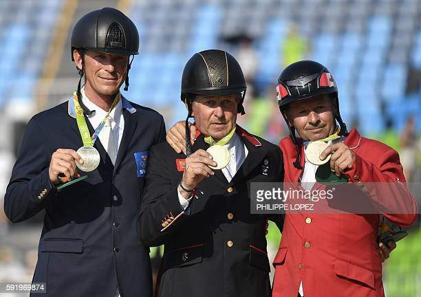 Britain's Nick Skelton poses with the gold medal next to Sweden's Peder Fredricson with the silver and Canada's Eric Lamaze with bronze after the...