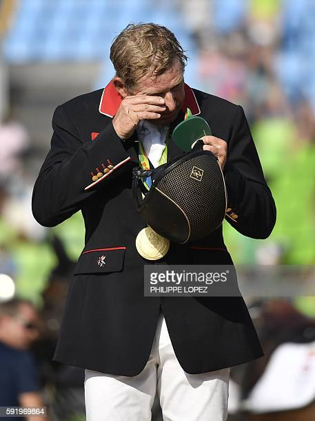 Britain's Nick Skelton wipes his face after getting his gold medal in the individual equestrian show jumping event at the Olympic Equestrian Centre...