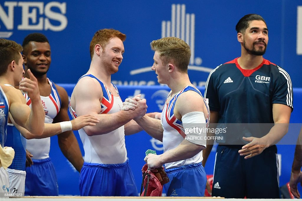 Britain's Nile Wilson (2nd R) is congratulated by his team-mate Daniel Purvis after the Mens Parallel Bars competition of the European Artistic Gymnastics Championships 2016 in Bern, Switzerland on May 28, 2016. / AFP / FABRICE