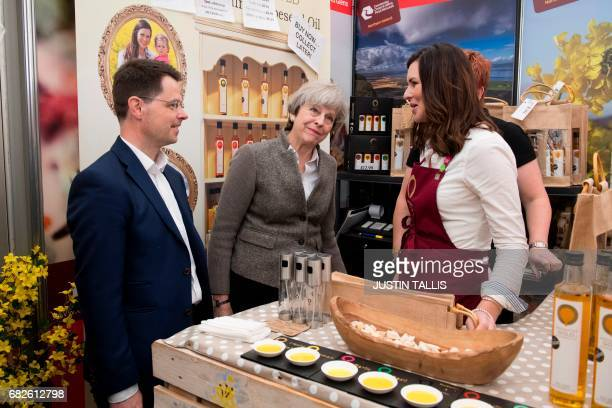 Britain's Northern Ireland Secretary James Brokenshire and British Prime Minister Theresa May speak with stall holders at the Balmoral Show near...
