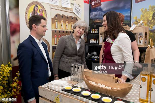 Britain's Northern Ireland Secretary James Brokenshire and British Prime Minister Theresa May speak with stall holders at the Balmoral Show during a...