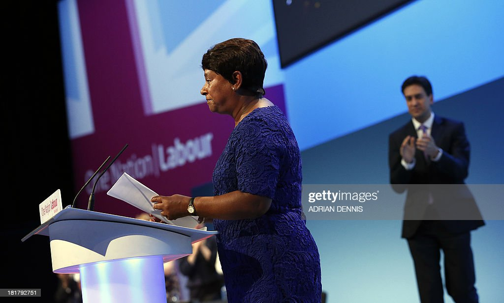 Britain's opposition Labour Party leader Ed Miliband (R) applauds Doreen Lawrence (L), mother of murdered teenager Stephen Lawrence, during the conclusion of the final day of the Labour party conference in Brighton, Sussex, south England on September 25, 2013. Britain's opposition Labour leader Ed Miliband positioned himself as the champion of hard-pressed working families, using a speech to his party's annual conference to promise a freeze on energy prices and higher wages.