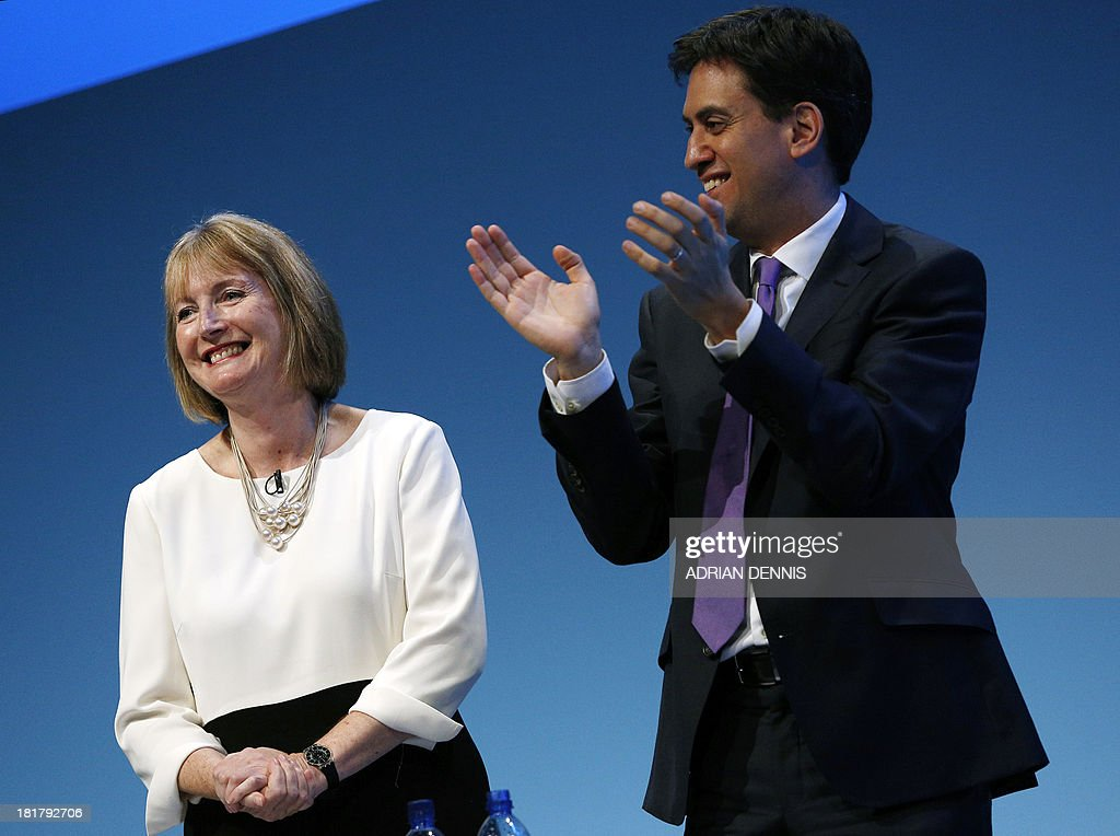 Britain's opposition Labour Party leader Ed Miliband (R) applauds Harriet Harman, Deputy Leader of the Labour Party, (L), following her speech during the conclusion of the final day of the Labour party conference in Brighton, Sussex, south England on September 25, 2013. Britain's opposition Labour leader Ed Miliband positioned himself as the champion of hard-pressed working families, using a speech to his party's annual conference to promise a freeze on energy prices and higher wages.