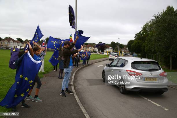 Britain's opposition Labour party leader Jeremy Corbyn drives past supporters holding EU flags outside a members' meeting as part of his summer...