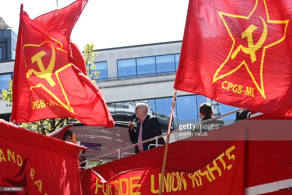 Britain's opposition Labour Party leader Jeremy Corbyn (C) gives a speech from the top of a double-decker bus as Communist Party of Great Britain (Marxist-Leninist) flags fly at a May Day rally in London on May 1, 2016. / AFP / JUSTIN