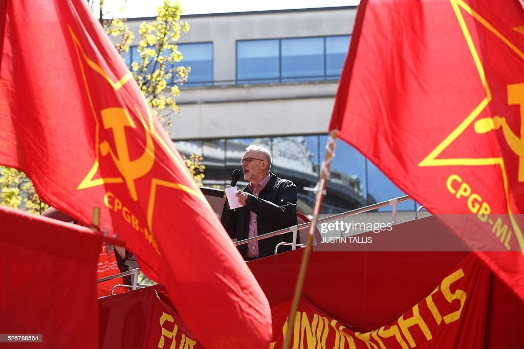 Britain's opposition Labour Party leader Jeremy Corbyn gives a speech from the top of a double-decker bus as Communist Party of Great Britain (Marxist-Leninist) flags fly at a May Day rally in London on May 1, 2016. / AFP / JUSTIN