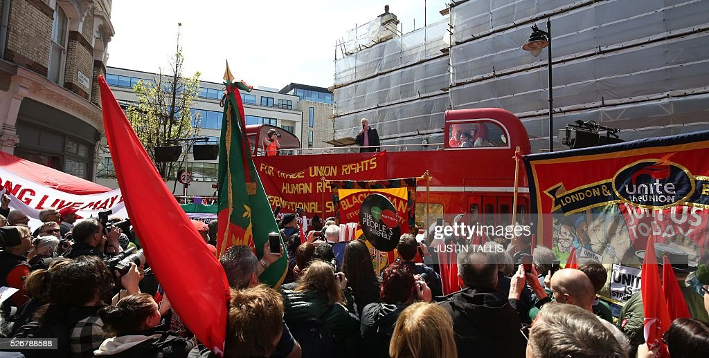 Britain's opposition Labour Party leader Jeremy Corbyn (C) gives a speech from the top of a double-decker bus at a May Day rally in London on May 1, 2016. / AFP / JUSTIN