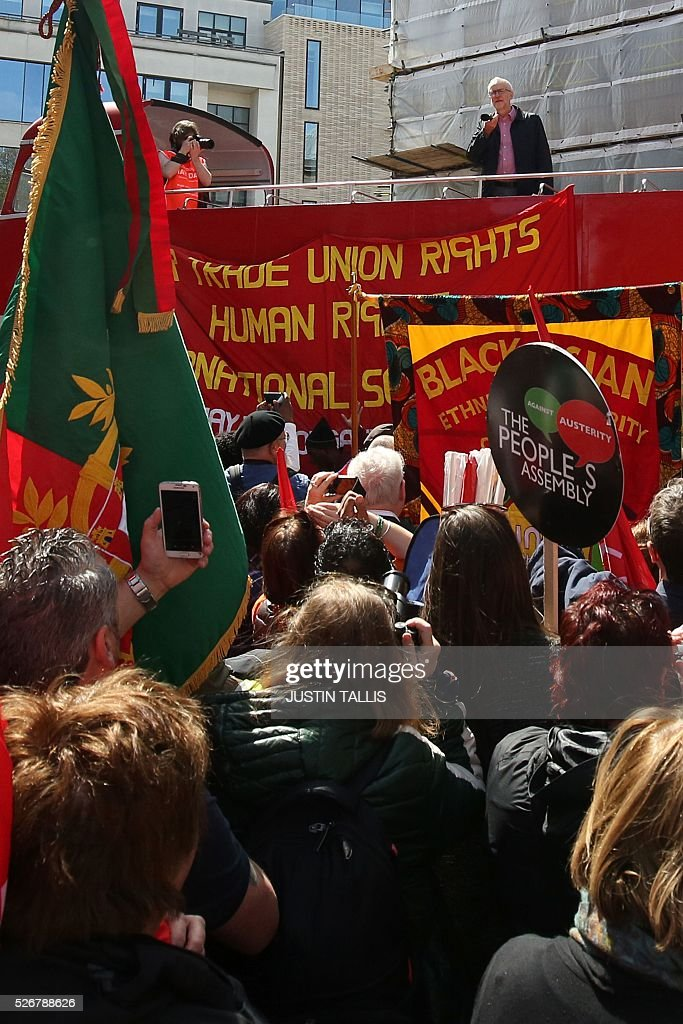 Britain's opposition Labour Party leader Jeremy Corbyn (R top) gives a speech from the top of a double-decker bus at a May Day rally in London on May 1, 2016. / AFP / JUSTIN
