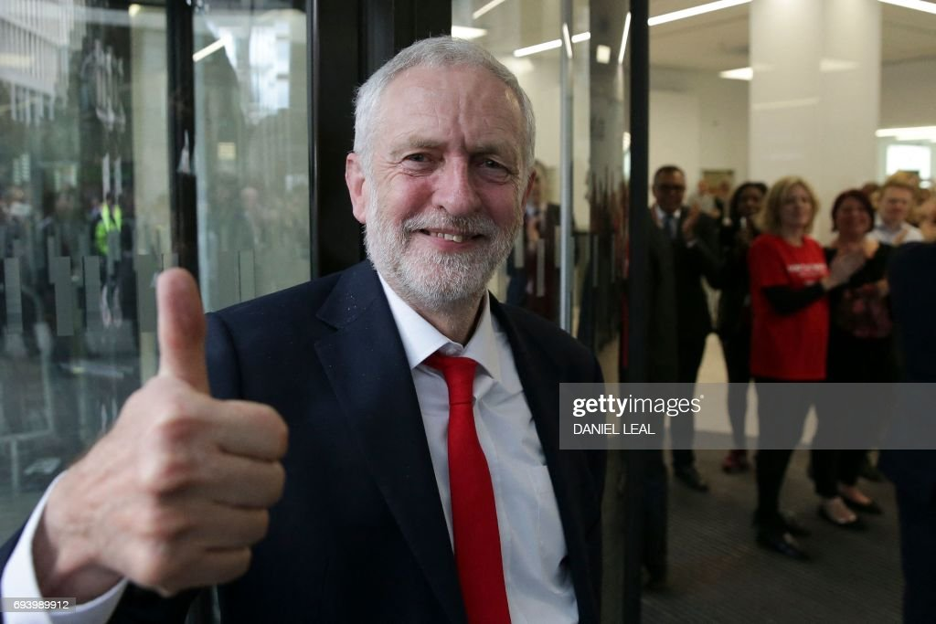 TOPSHOT - Britain's opposition Labour party Leader Jeremy Corbyn gives a thumbs up as he arrives at Labour Party headquarters in central London on June 9, 2017 after results in a snap general election showing a hung parliament with Labour gains and the Conservatives losing its majority. British Prime Minister Theresa May faced pressure to resign on Friday after losing her parliamentary majority, plunging the country into uncertainty as Brexit talks loom. The pound fell sharply amid fears the Conservative leader will be unable to form a government and could even be forced out of office after a troubled campaign overshadowed by two terror attacks. / AFP PHOTO / Daniel LEAL