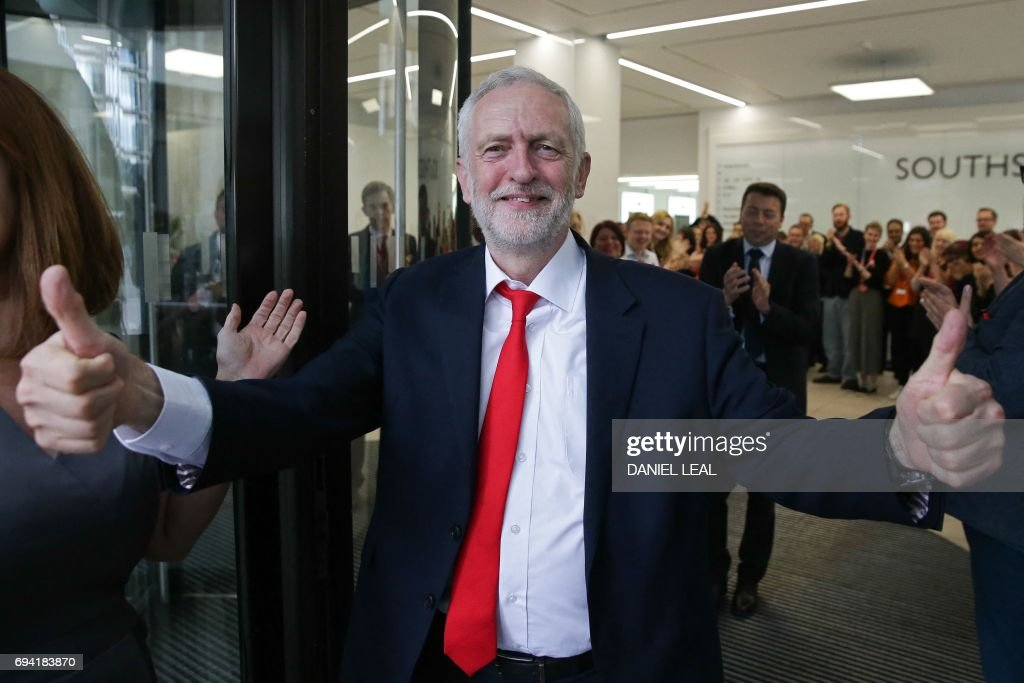 Britain's opposition Labour party Leader Jeremy Corbyn gives a thumbs up as he arrives at Labour Party headquarters in central London on June 9, 2017 after results in a snap general election showing a hung parliament with Labour gains and the Conservatives losing its majority. British Prime Minister Theresa May faced pressure to resign on Friday after losing her parliamentary majority, plunging the country into uncertainty as Brexit talks loom. The pound fell sharply amid fears the Conservative leader will be unable to form a government and could even be forced out of office after a troubled campaign overshadowed by two terror attacks. / AFP PHOTO / Daniel LEAL