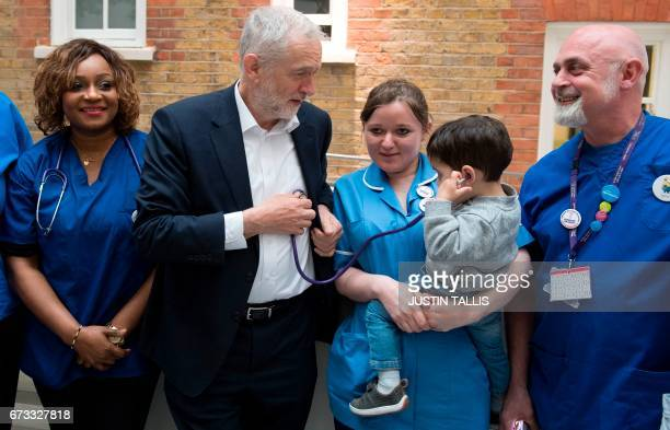 Britain's opposition Labour Party leader Jeremy Corbyn listens through a stethoscope with Haroon whilst meeting with nurses and other medical staff...