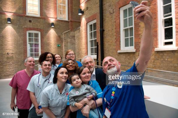 Britain's opposition Labour Party Leader Jeremy Corbyn poses for a selfie with nurses and other medical staff during a general election campaign...