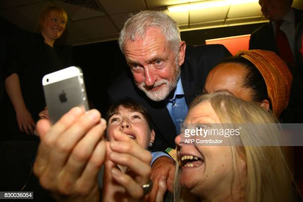 Britain's opposition Labour party leader Jeremy Corbyn poses for a selfie with supporters at a members' meeting as part of his summer campaign tour...