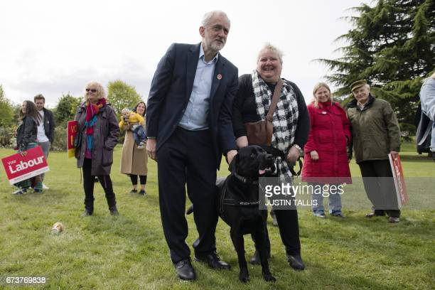 Britain's opposition Labour Party Leader Jeremy Corbyn poses with a supporter and her dog during a campaign event in Harlow Town Park Essex north of...
