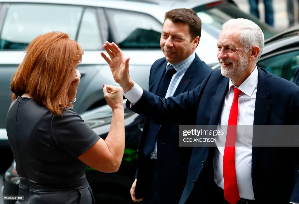Britain's opposition Labour party Leader Jeremy Corbyn (R) reacts as he is greeted by Karie Murphy, a member of his campaign team, as he arrives at Labour Party headquarters in central London on June 9, 2017 after results in a snap general election showing a hung parliament with Labour gains and the Conservatives losing its majority. British Prime Minister Theresa May faced pressure to resign on Friday after losing her parliamentary majority, plunging the country into uncertainty as Brexit talks loom. The pound fell sharply amid fears the Conservative leader will be unable to form a government and could even be forced out of office after a troubled campaign overshadowed by two terror attacks. / AFP PHOTO / Odd ANDERSEN