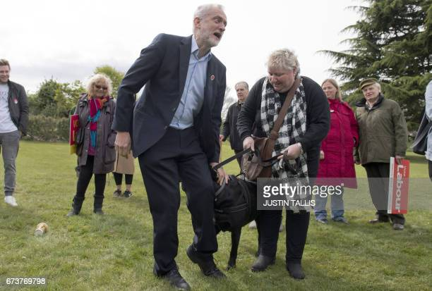 Britain's opposition Labour Party Leader Jeremy Corbyn reacts to the dog as he poses with a supporter and her dog during a campaign event in Harlow...