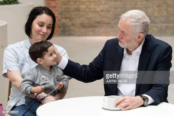 Britain's opposition Labour Party leader Jeremy Corbyn sits during a round table discussion with nurses other medical staff and students and Haroon...