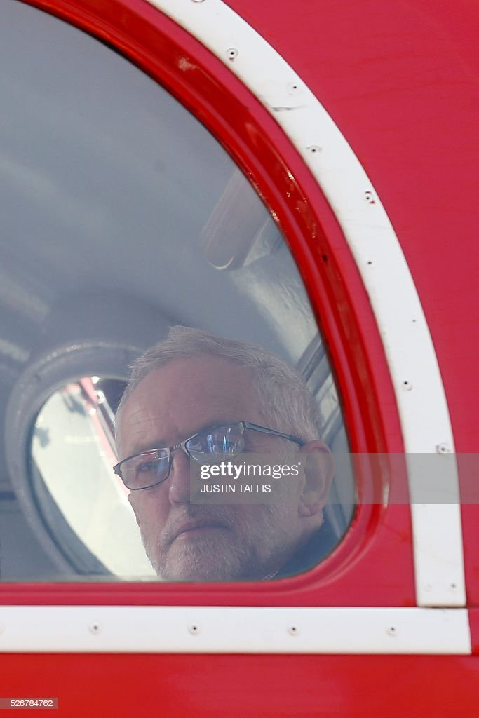 Britain's opposition Labour Party leader Jeremy Corbyn sits on a double decker bus ahead of giving a speech at a May Day rally in London on May 1, 2016. / AFP / JUSTIN