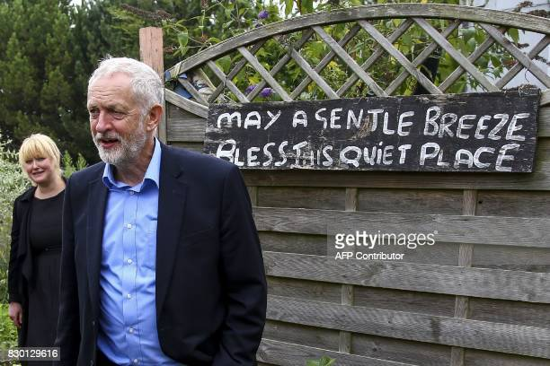 Britain's opposition Labour Party Leader Jeremy Corbyn stands beside a painted slogan in the kitchen garden of the Manor Garden Centre in Swindon...