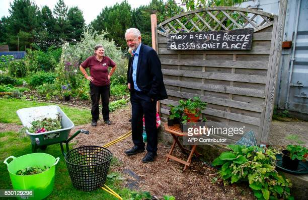 Britain's opposition Labour Party Leader Jeremy Corbyn walks in the kitchen garden of the Manor Garden Centre in Swindon west of London on August 11...