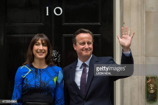 Britain's Prime Minister and Leader of the Conservative Party David Cameron and his wife Samantha pose for pictures as they arrive back at 10 Downing...