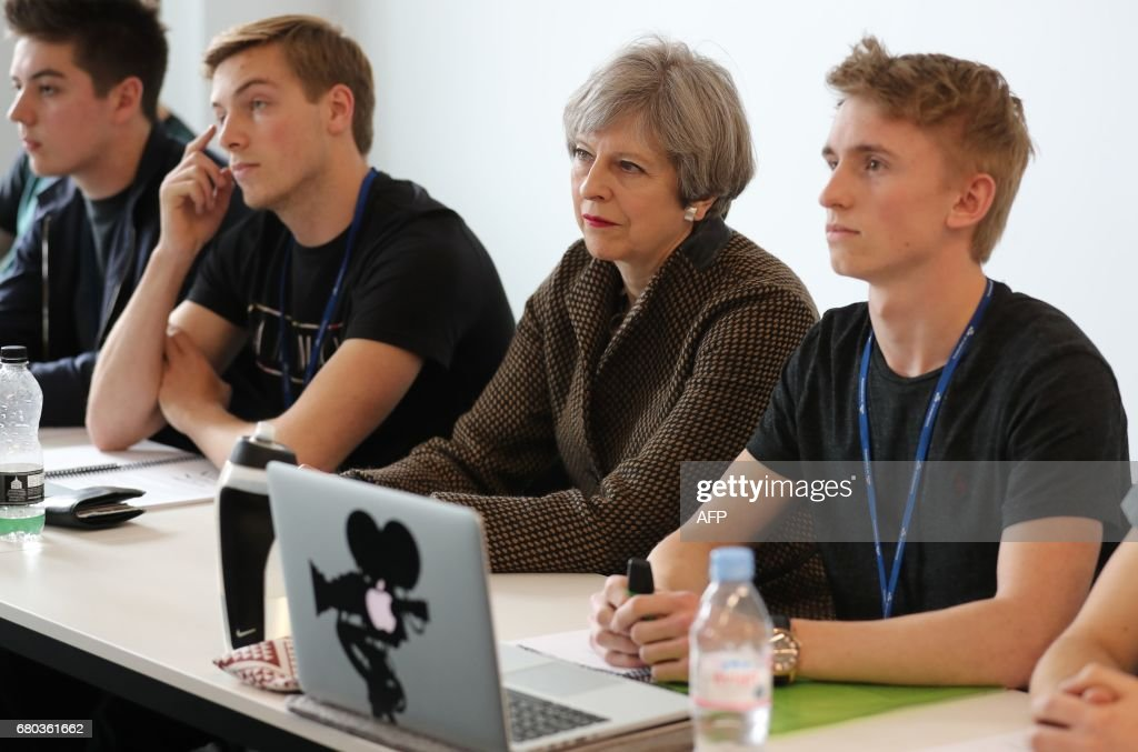 Britain's Prime Minister and leader of the Conservative Party Theresa May (2R) meets with students during a campaign visit to the International Aviation Academy in Norwich, eastern England, on May 8, 2017. Campaigning continues in the build up to Britain's general election on June 8. / AFP PHOTO / POOL / Chris Radburn