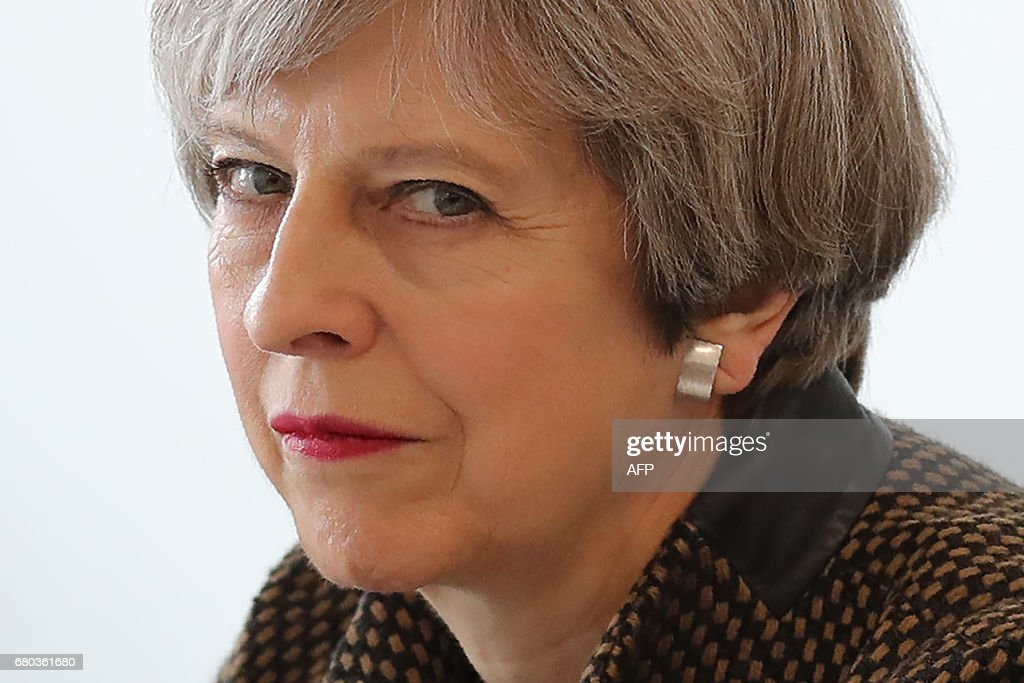 Britain's Prime Minister and leader of the Conservative Party Theresa May meets with students during a campaign visit to the International Aviation Academy in Norwich, eastern England, on May 8, 2017. Campaigning continues in the build up to Britain's general election on June 8. / AFP PHOTO / POOL / Chris Radburn