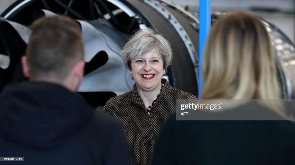 Britain's Prime Minister and leader of the Conservative Party Theresa May (C) meets with people during a campaign visit to the International Aviation Academy in Norwich, eastern England, on May 8, 2017. Campaigning continues in the build up to Britain's general election on June 8. / AFP PHOTO / POOL / Chris Radburn