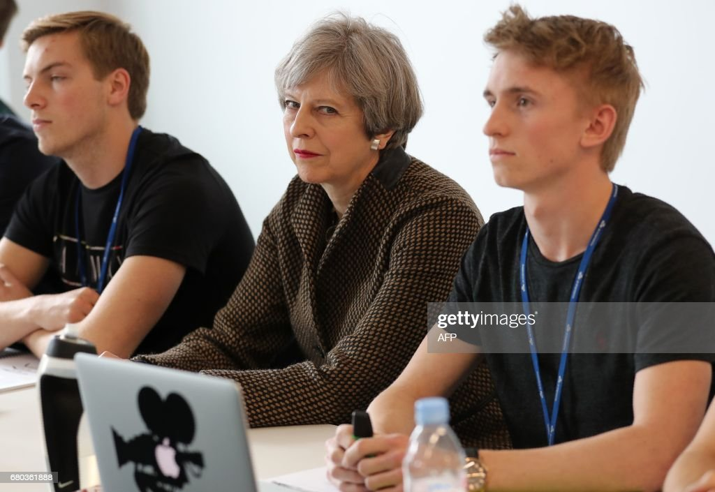Britain's Prime Minister and leader of the Conservative Party Theresa May (C) meets with students during a campaign visit to the International Aviation Academy in Norwich, eastern England, on May 8, 2017. Campaigning continues in the build up to Britain's general election on June 8. / AFP PHOTO / POOL / Chris Radburn
