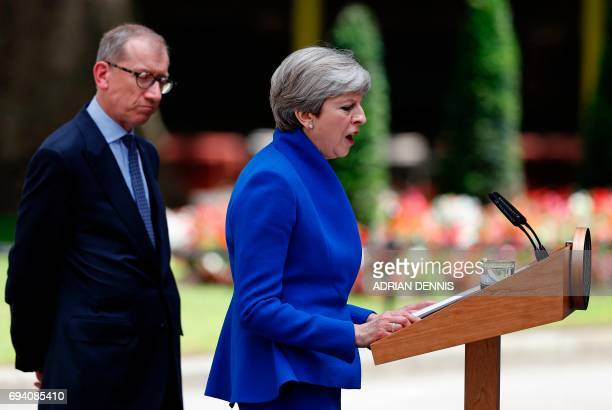 Britain's Prime Minister and leader of the Conservative Party Theresa May accompanied by her husband Philip delivers a statement outside 10 Downing...