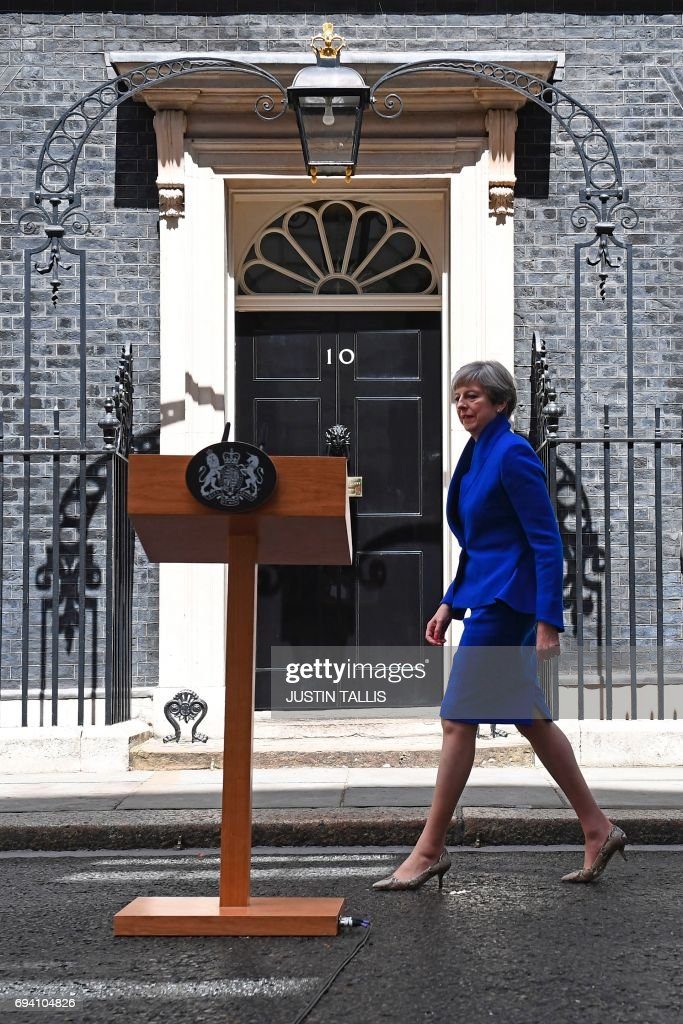 Britain's Prime Minister and leader of the Conservative Party Theresa May approaches the lecturn to deliver a statement outside 10 Downing Street in central London on June 9, 2017 as results from a snap general election show the Conservatives have lost their majority. British Prime Minister Theresa May said Friday she planned to stick to the timetable for starting Brexit negotiations in 10 days, with a new government that would lead Britain out of the EU. / AFP PHOTO / Justin TALLIS