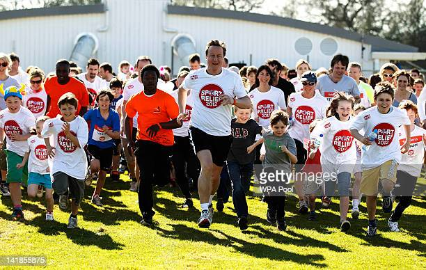 Britain's Prime Minister David Cameron accompanied by his wife Samantha starts a mile race for Sports Relief charity on March 25 2012 near Great...